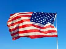 De vlagvliegen van de V.S. in de blauwe hemel aan de wind van vrijheid stock afbeelding