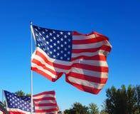 De vlagvliegen van de V.S. in de blauwe hemel aan de wind van vrijheid stock afbeeldingen