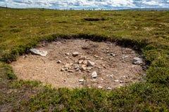 De vlakke mening van het hooglandlandschap van een groot die gat in de grond door groene vegetatie wordt omringd stock afbeelding