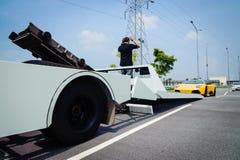 De vlakke vrachtwagen die van het bedslepen een gebroken voertuig laden Stock Fotografie