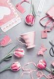 De vlakte van het de lentestilleven legt met pastelkleur roze tulpen, harten, mok, giften, markeringen en schaar, hoogste mening  Stock Fotografie