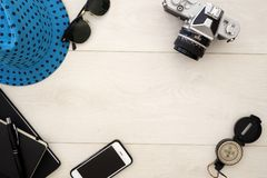 De vlakte van het reisconcept legt overheadkosten op wit hout, met camera en zonglazen stock afbeeldingen