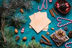 De vlakte van de Kerstmisviering legt met ambachtdocument, kegels en suikergoeddames met exemplaarruimte op groene achtergrond Stock Foto's