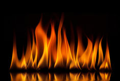 De vlammen van de brand op een zwarte achtergrond stock afbeeldingen