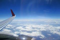 De vleugel van het vliegtuig tegen de wolken royalty-vrije stock afbeelding
