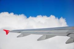 De vleugel van vliegtuigen door de wolken Stock Fotografie