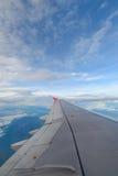De vleugel van vliegtuigen op de wolken Stock Afbeelding