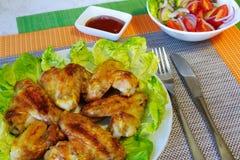De vleugels van de kip en plantaardige salade stock foto's