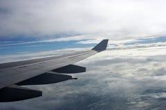 De vleugels van het vliegtuig over wolken Stock Foto