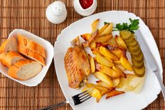 De vleugels van Turkije bakten met aardappelstukken op een witte plaat met een waarde van een bamboeservet met tartaarsaus en tom royalty-vrije stock foto's