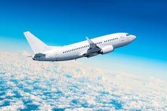 De vlieg van het passagiersvliegtuig op een hoogte boven donkere wolken en blauwe hemel royalty-vrije stock afbeeldingen