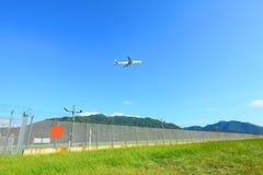 De vlieg van het vliegtuig over grassen in dagtijd Stock Foto