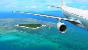 De Vliegen van het passagiersvliegtuig over Tropisch Eiland stock afbeeldingen