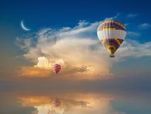 De vliegen van hete luchtballons in gloeiende zonsonderganghemel boven kalme overzees Stock Fotografie