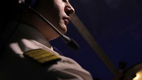 De vlieger kleedde zich in eenvormig met epauletten die vliegtuig, professioneel op het werk vliegen stock footage