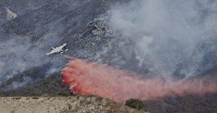 De vliegtuigdalingen steken retardent op brand in brand Stock Foto
