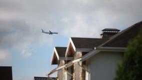De vliegtuigen op het landen benadering over huisvesting in de voorsteden stock videobeelden