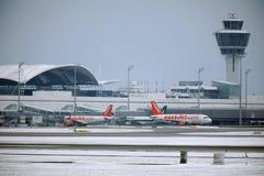 De vliegtuigen van EasyJet en Alitalia-bij eindpoorten in de Luchthaven van München, sneeuw stock afbeeldingen