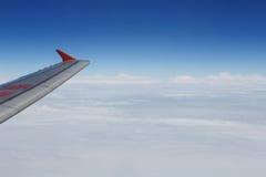 De vliegtuigenturbine die van de vliegtuigvleugel blauwe hemel witte wolken vliegen Stock Fotografie