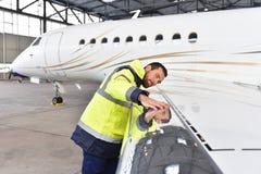 De vliegtuigenwerktuigkundige inspecteert en controleert de technologie binnen van een straal stock foto's