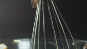 De vloeibare chocolade stroomt onderaan de rand, wordt de rand ondergedompeld in een glascontainer en de chocolade is gestoord, g stock video