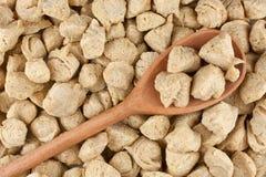 De vlokken van de soja in houten lepel Stock Afbeeldingen