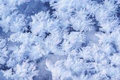 De vlokken van het ijs op blauwe bevroren achtergrond Stock Afbeeldingen