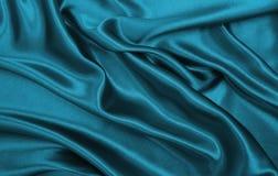 De vlotte elegante blauwe zijde of satijntextuur van de luxedoek als abstra stock fotografie