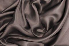 De vlotte elegante blauwe zijde of satijntextuur van de luxedoek als abstra stock foto