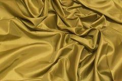De vlotte elegante gouden zijde of satijntextuur van de luxedoek kan a gebruiken royalty-vrije stock fotografie