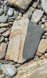 De vlotte kiezelsteenstenen op de kust zijn grijze droog stock foto's