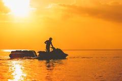 De vlotter van de banaanboot met straalski in het overzees en de zonsondergang stock afbeelding