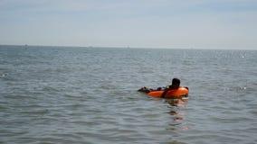 De vlotters van de tienerjongen bij Britse kust op opblaasbare matras stock video