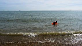 De vlotters van de tienerjongen bij Britse kust op opblaasbare matras stock footage