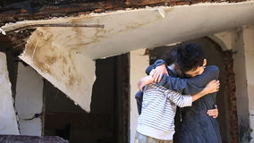 De vluchtelingskinderen zitten dichtbij een geruïneerd huis Oorlog, aardbeving, brand, het bombarderen