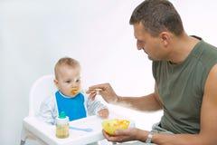 De voedende baby van de mens met een lepel Royalty-vrije Stock Foto's