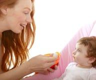 De voedende baby van de moeder gele lepel Royalty-vrije Stock Afbeeldingen