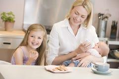 De voedende baby van de moeder met dochter het eten stock fotografie