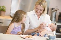 De voedende baby van de moeder met dochter het eten stock foto