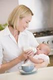 De voedende baby van de moeder met koffie het glimlachen stock afbeeldingen