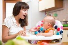 De voedende baby van de moeder met lepel stock foto