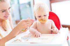 De voedende baby van de moeder met lepel Stock Fotografie
