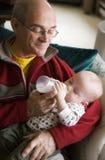 De voedende baby van de opa Stock Foto's