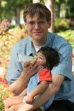 De voedende baby van de vader een fles in het park Stock Foto