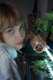 De voedende vissen van het meisje in aquarium Stock Afbeelding
