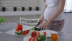 De voeding van zwangere vrouwen, verwachtend wijfje met grote maag kookt nuttige maaltijd voor gezonde smakelijke brunch van stock videobeelden