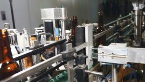 De voedselindustrie Automatische Bier Bottellijn Het toepassen van het etiket Machine om etiketten voor bierflessen te kleven 4K stock footage