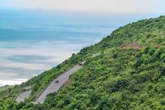 De voertuigen kruisen aan een multilaagweg die op een berg gaan kijkend ontzagwekkend met strandachtergrond stock foto