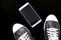 De voet in de tennisschoenen en gebroken telefoon op zwarte achtergrond royalty-vrije stock afbeeldingen