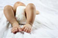 De Voet van de baby van Aziatische Zuigeling op een bed royalty-vrije stock fotografie